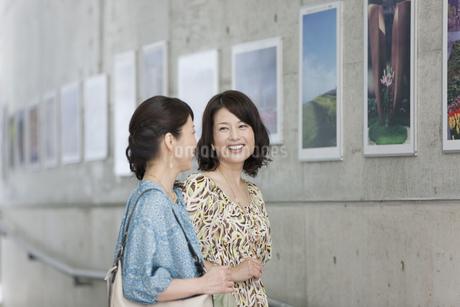写真の前で話す中高年女性2人の写真素材 [FYI02931335]