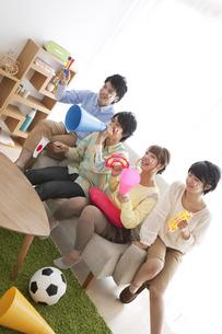 ソファーに座って応援する男女4人の写真素材 [FYI02931374]