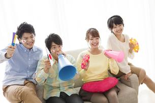 ソファーに座って応援する男女4人の写真素材 [FYI02931382]