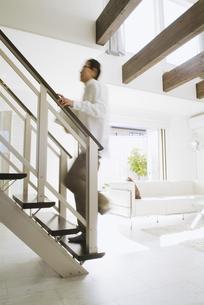 新聞を抱えて階段を登る中高年男性の写真素材 [FYI02931464]
