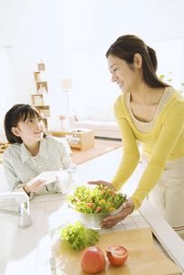 キッチンでサラダボウルを持つ母と娘の写真素材 [FYI02931478]