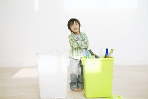 2つのゴミ箱の前で考える男の子の写真素材 [FYI02931479]