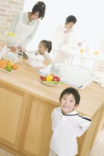 笑顔の兄とキッチンに立つ母娘の写真素材 [FYI02931484]