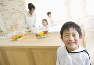 笑顔の兄とキッチンに立つ母娘の写真素材 [FYI02931490]