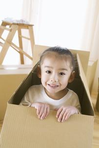 ダンボール箱の中から顔を出す女の子の写真素材 [FYI02931500]