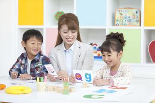 英語を勉強する子供と先生の写真素材 [FYI02931694]