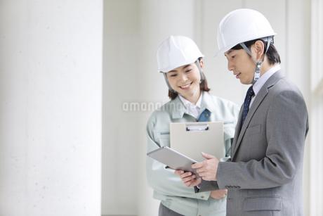 建設現場で打ち合わせをする男女2人の写真素材 [FYI02931717]