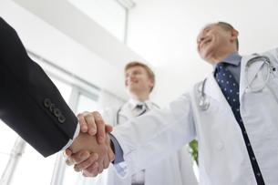 握手をする医師とビジネスマンの手元の写真素材 [FYI02931856]
