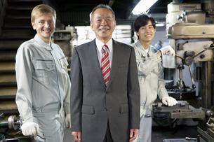 笑顔のビジネスマンと作業者2人の写真素材 [FYI02931858]