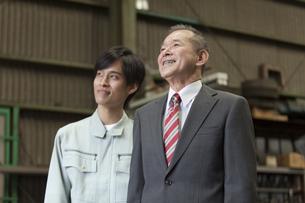 笑顔のビジネスマンと作業者の写真素材 [FYI02931859]