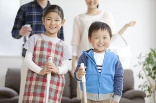 掃除道具を持つ女の子と男の子の写真素材 [FYI02931871]