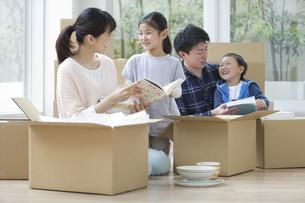 引っ越しの荷造りをする家族4人の写真素材 [FYI02931878]