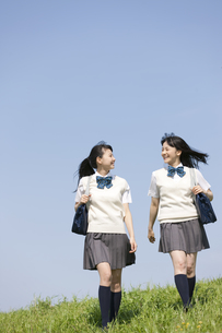 芝生を歩く女子校生2人の写真素材 [FYI02931904]