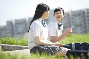 土手に座って話をする女子校生2人の写真素材 [FYI02931910]