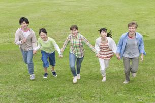 手をつないで走る若者5人の写真素材 [FYI02931924]