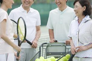 テニスコートで話す男女4人の写真素材 [FYI02931956]