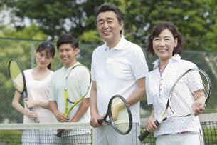 テニスコートに立つ男女4人の写真素材 [FYI02931958]