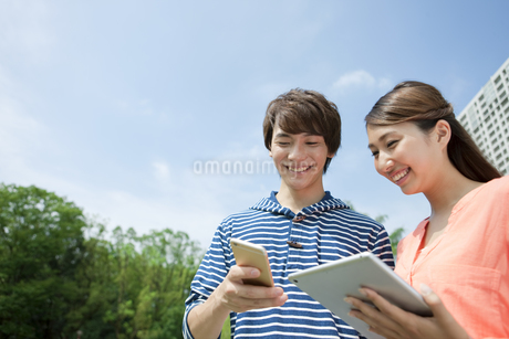 電子機器を見るカップルの写真素材 [FYI02932017]