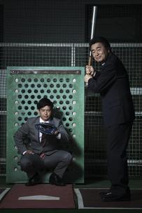 バッティングセンターにいるビジネスマン2人の写真素材 [FYI02932064]