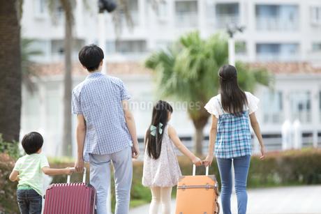 スーツケースを引いて歩く4人家族の写真素材 [FYI02932133]