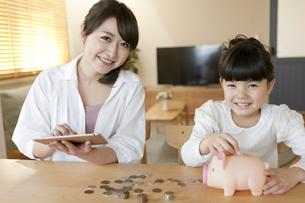 貯金箱と親子の写真素材 [FYI02932160]