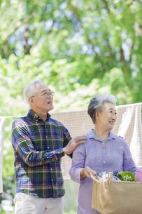 洗濯物を持つシニア夫婦の写真素材 [FYI02932176]