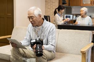 タブレットPCとカメラを持つシニア男性の写真素材 [FYI02932294]