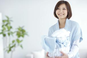洗濯カゴを抱えている笑顔の女性の写真素材 [FYI02932351]
