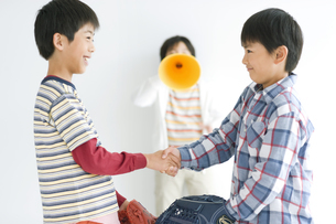 握手する男の子達と応援する男の子の写真素材 [FYI02932428]
