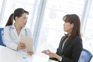 打ち合わせをする女医とビジネスウーマンの写真素材 [FYI02932464]