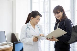 打ち合わせをする女医とビジネスウーマンの写真素材 [FYI02932465]