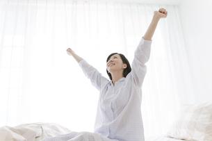 ベッドで伸びをする中高年女性の写真素材 [FYI02932676]