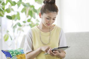 タブレットPCを操作する女性の写真素材 [FYI02932696]