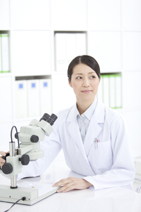 顕微鏡を操作する女性研究員の写真素材 [FYI02932808]