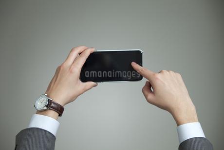 スマートフォンを操作するビジネスマンの手元の写真素材 [FYI02932836]