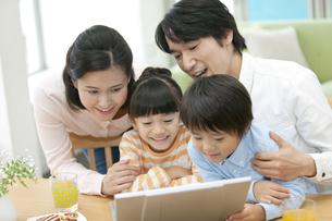 ノートパソコンを見ている家族4人の写真素材 [FYI02933017]