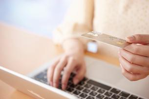 クレジットカードを持ちパソコンを打つ女性の手の写真素材 [FYI02933324]