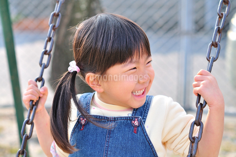 公園のブランコで遊ぶ女の子の写真素材 [FYI02933544]