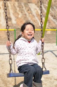 公園のブランコで遊ぶ女の子の写真素材 [FYI02933582]