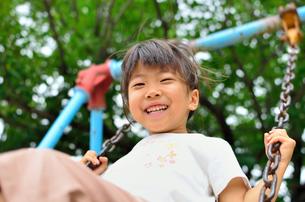 公園のブランコで遊ぶ女の子の写真素材 [FYI02933646]