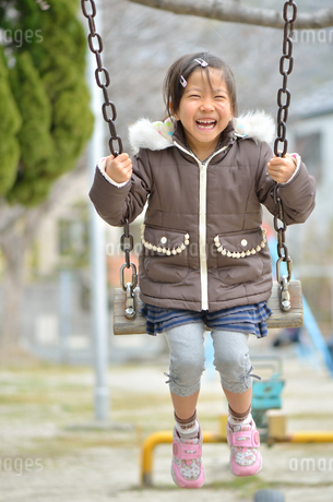 公園のブランコで遊ぶ女の子の写真素材 [FYI02933710]