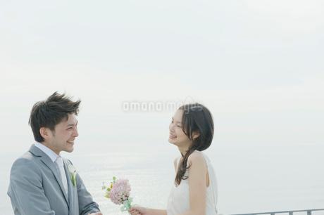 海辺のテラスで向かい合い談笑する花嫁と花婿の写真素材 [FYI02933737]