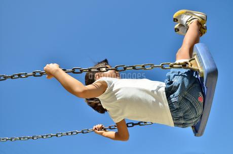 公園のブランコで遊ぶ女の子の写真素材 [FYI02933741]
