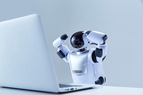 ノートパソコンを操作するミニロボットの写真素材 [FYI02933747]