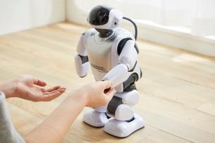 女性に手を握られているロボットの写真素材 [FYI02933749]