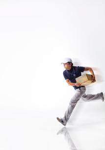 白バックの空間で荷物を持って走る作業着の男性の写真素材 [FYI02933752]