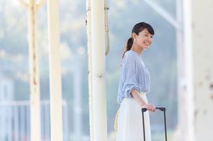 駅のホームで電車を待つ女性の写真素材 [FYI02933753]