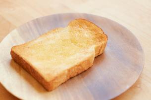 木の皿の上に置かれたバターが塗られた食パンの写真素材 [FYI02933757]