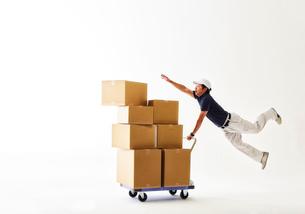 白バックの空間で台車の荷物を落としかけて飛ぶ作業着の男性の写真素材 [FYI02933758]