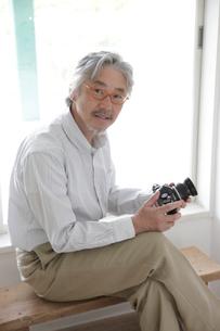 古いカメラを持つミドル男性の写真素材 [FYI02933769]